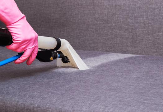 Image of dirty sofa being cleaned by an upholstery cleaning hand tool.