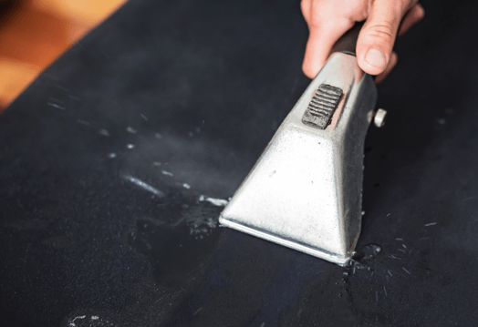 Image of a fabric cover being cleaned using a upholstery cleaning hand tool.